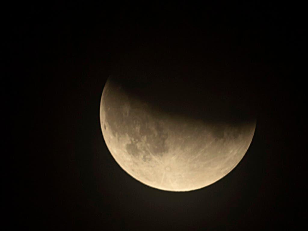 Blick auf den sich Mond teils im Erdschatten befindenen Mond kurz nach Mitternacht in Basel. (Bild: KEYSTONE/Georgios Kefalas)
