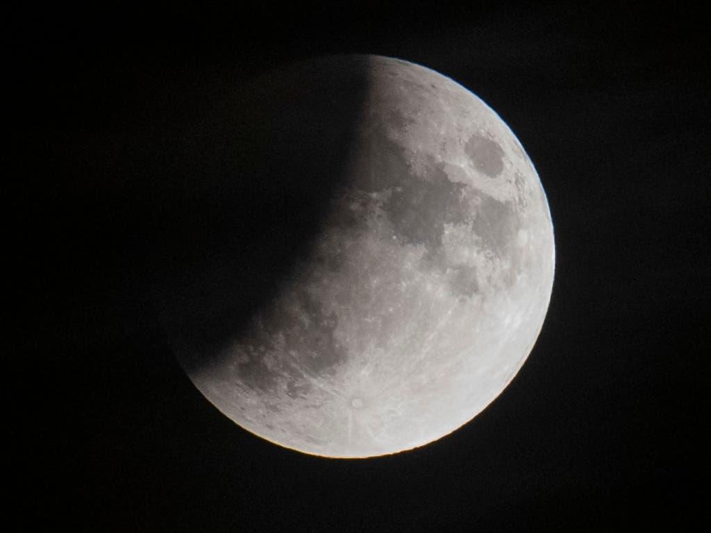 Eine partielle Mondfinsternis aufgenommen über den Dächern Zürichs. (Bild: KEYSTONE/Ennio Leanza)