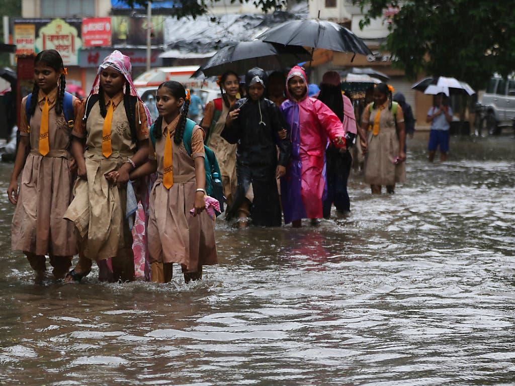 Schulkinder waten in der Millionenstadt Mumbai durch eine vom Monsunregen überschwemmte Strasse. (Bild: KEYSTONE/AP/RAFIQ MAQBOOL)