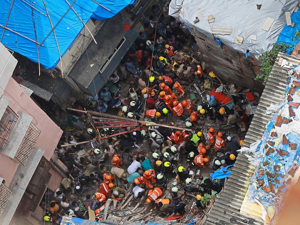 Helfer- und Rettungsteams suchen nach dem Einsturz eines Hauses in Mumbai nach Verschütteten. (Bild: KEYSTONE/EPA/DIVYAKANT SOLANKI)