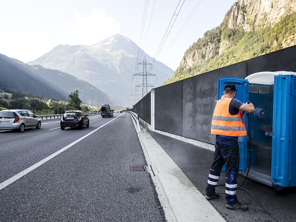 Alexandar Djordjevic reinigt mobile Toilettenkabinen direkt an der Autobahn A2 vor dem Gotthard-Nordportal bei Wassen. (Bild: KEYSTONE/ALEXANDRA WEY)
