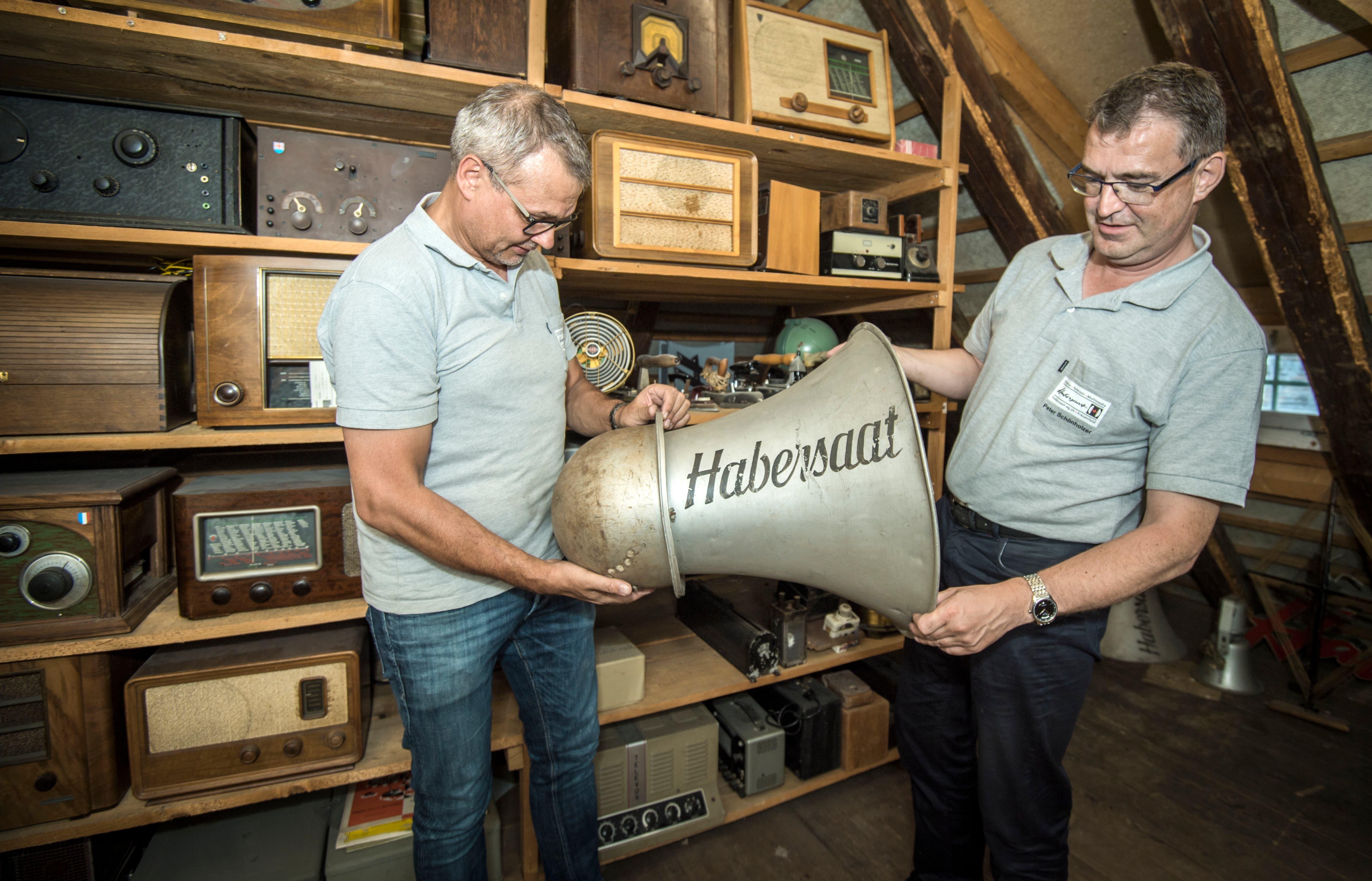 Die Firma stellte auch Lautsprecher her. Stefan Habersaat und Peter Schönholzer heben den schweren Trichter hoch.