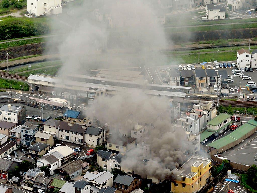Nach dem verheerenden Brandanschlag auf ein Filmstudio in Kyoto steigt eine Rauchsäule über dem Gebäude auf. (Bild: KEYSTONE/AP Kyodo News)