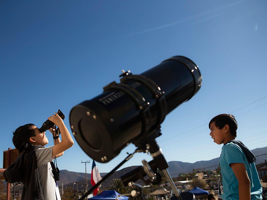 Auch Kinder in Chile testen Feldstecher, um die Sonnenfinsternis zu beobachten. (Bild: KEYSTONE/AP/ESTEBAN FELIX)