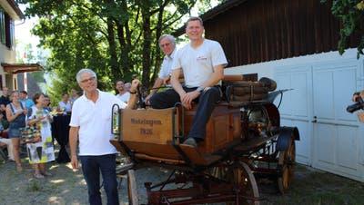 Museumspräsident Elmar Bissegger, Vorstandsmitglied Hansueli Zuberbühler und Feuerwehrkommandant Christian Büchi posieren bei der Motorspritze von 1926. (Bild: Manuela Olgiati)