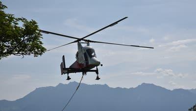 Der K-Max-Helikopter mit einem Hebevermögen von 2,7 Tonnen flog am Freitag die gefällten Fichten aus dem Schutzwald. (Bild: Heini Schwendener)