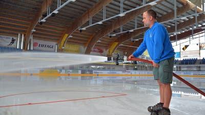 Benjamin Fretz sprüht Wasser mit dem Feuerwehrschlauch auf die Eisfläche in der Güttingersreuti. (Bild: Mario Testa)