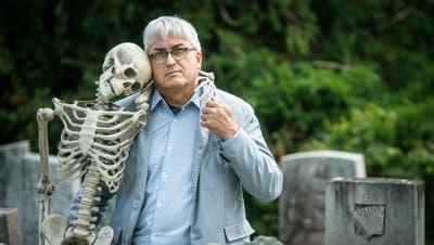 Der Tod macht ihm keine Angst: Pfarrer Marcel Ruepp mit Skelett auf dem Friedhof von Wuppenau. (Bild: Reto Martin)