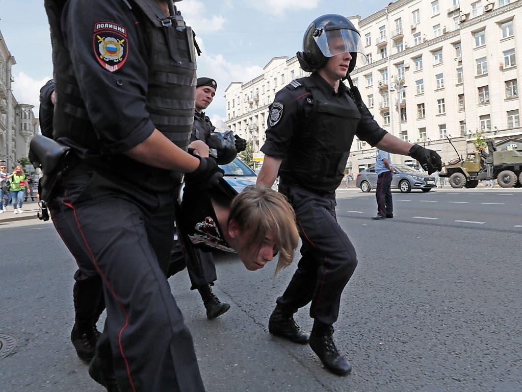 Russische Polizisten führen einen Kundgebungsteilnehmer vor dem Moskauer Rathaus ab. (Bild: KEYSTONE/EPA/YURI KOCHETKOV)