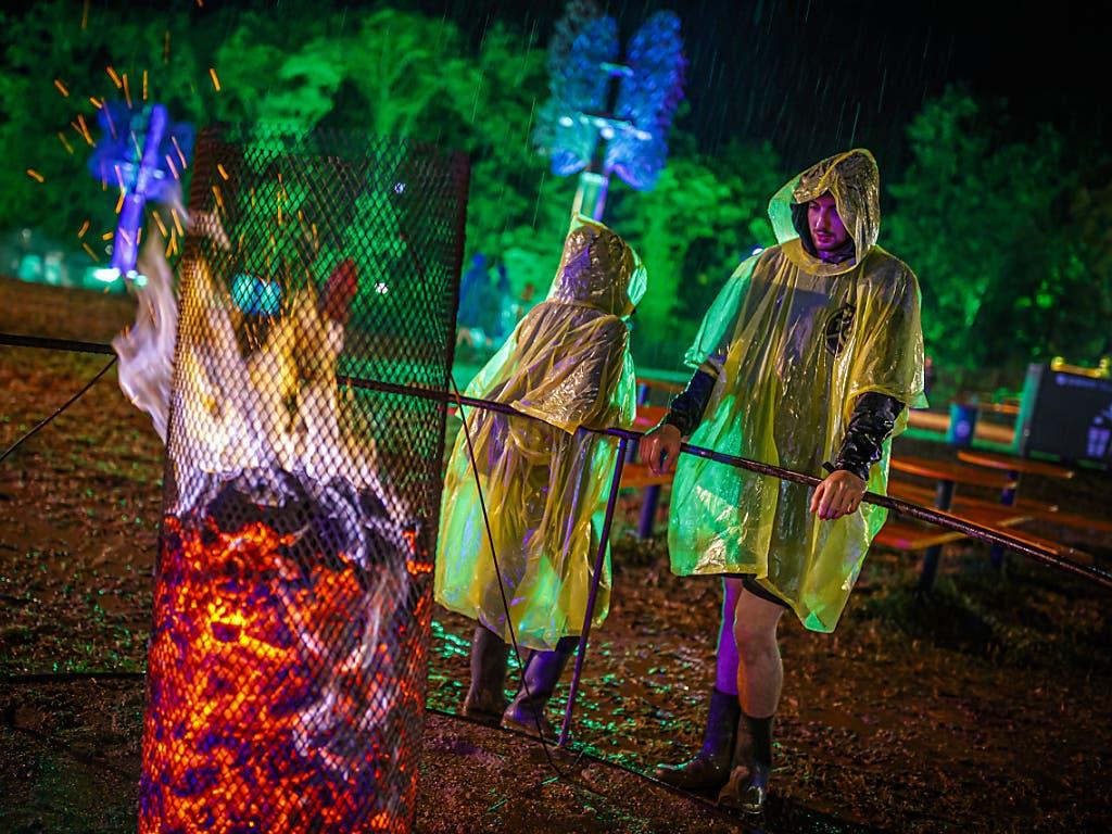 Das 44. Paléo Festival in Nyon ging am Sonntag zu Ende: Auch der Regen konnten dem Openair nichts anhaben. Besucher in Regenpellerinen stehen an einer Feuerstelle. (Bild: KEYSTONE/VALENTIN FLAURAUD)