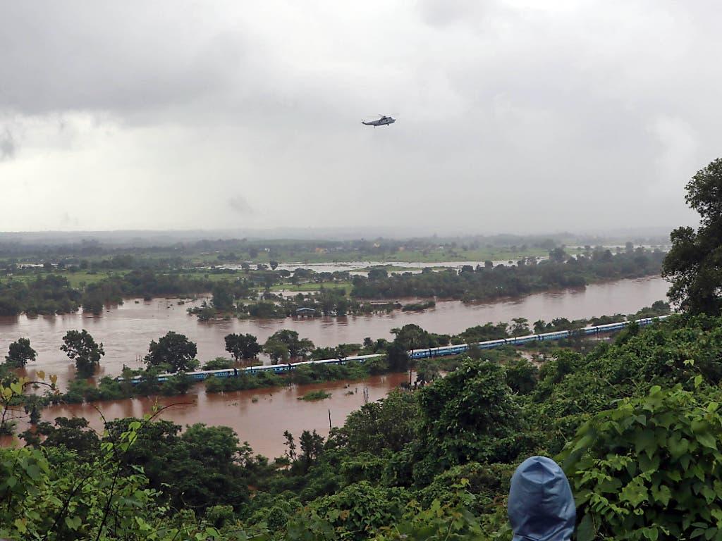 Aus dem in den Monsunfluten stecken gebliebenen Zug wurden im Südwesten Indiens fast 900 Reisende mit Booten und Helikoptern in Sicherheit gebracht. (Bild: KEYSTONE/AP/MAHESH MORE)