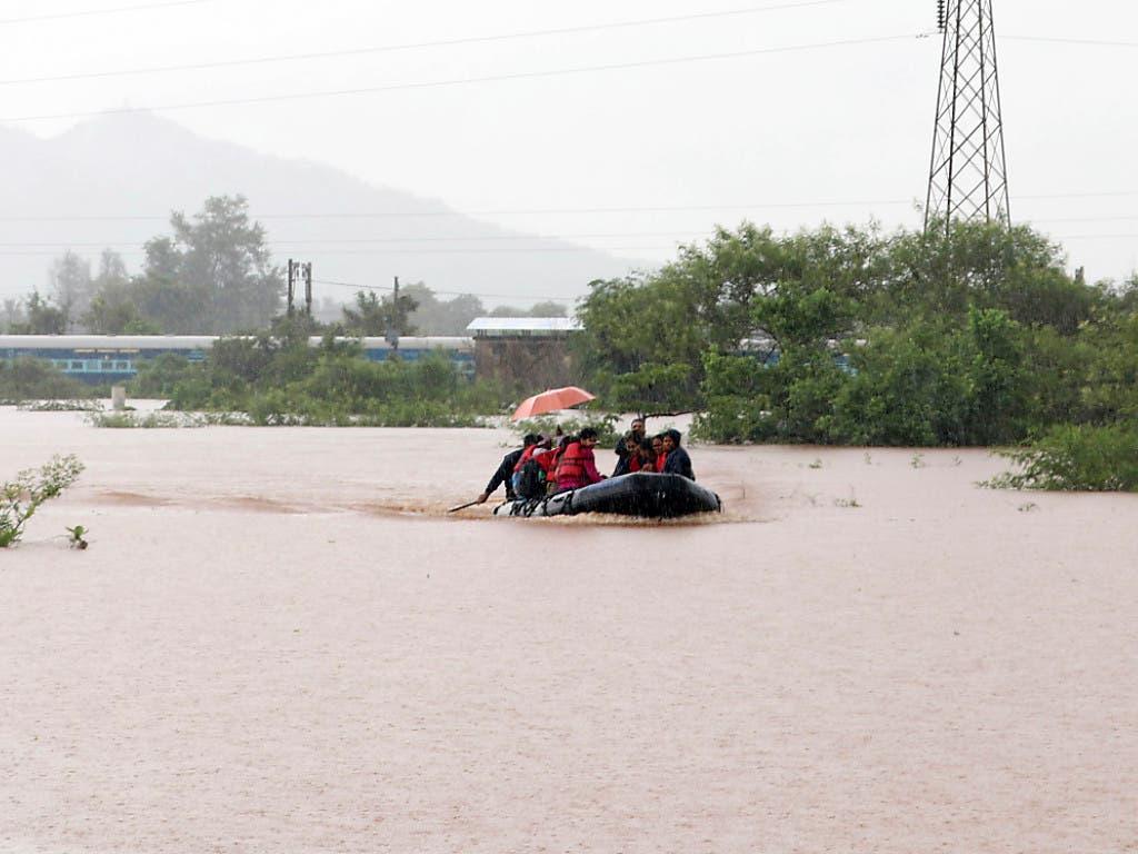 Rettung per Boot: fast 900 Passagiere befanden sich im Südwesten Indiens in einem Zug, der in Monsunfluten stecken blieb. (Bild: KEYSTONE/AP/MAHESH MORE)