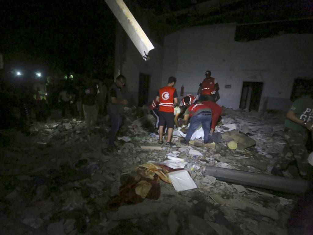 Mitarbeiter der Hilfsorganisation Roter Halbmond bergen Opfer nach dem Luftangriff auf ein Flüchtlingslager im Vorort Tajoura nahe der libyschen Hauptstadt Tripolis. (Bild: KEYSTONE/AP/HAZEM AHMED)
