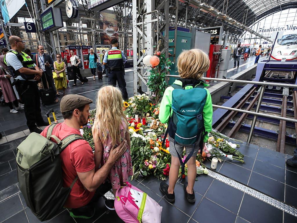 Passanten legen am Gleis im Frankfurter Hauptbahnhof, an dem der achtjährige Bub starb, Blumen nieder. (Bild: KEYSTONE/EPA/ARMANDO BABANI)