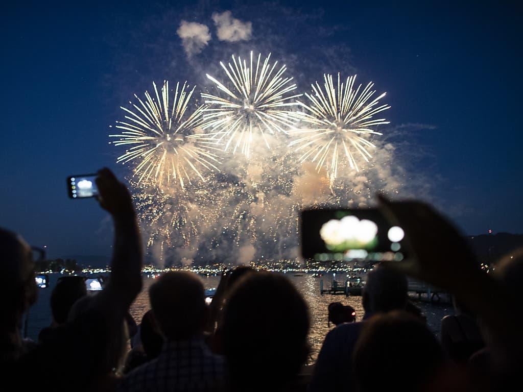 Besucher bestaunen das Feuerwerk vom Ufer des Zürichsees aus. (Bild: KEYSTONE/ENNIO LEANZA)