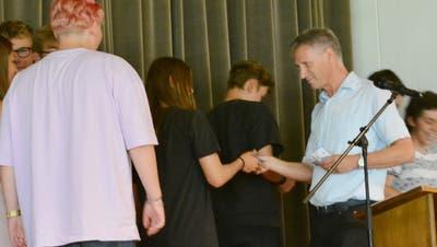 Arno Germann verteilt Gutscheine an die Schülerinnen und Schüler, die als Gotti und Götti im neuen Schuljahr Erstklässlerunter ihre Fittiche nehmen. (Bild: Judith Schuck)
