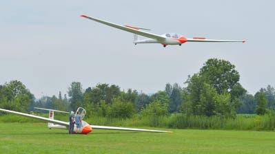 Der eine Segelflieger steht zum Start bereit, ein anderer setzt in diesem Moment zur Landung an. (Bild: Mario Testa)