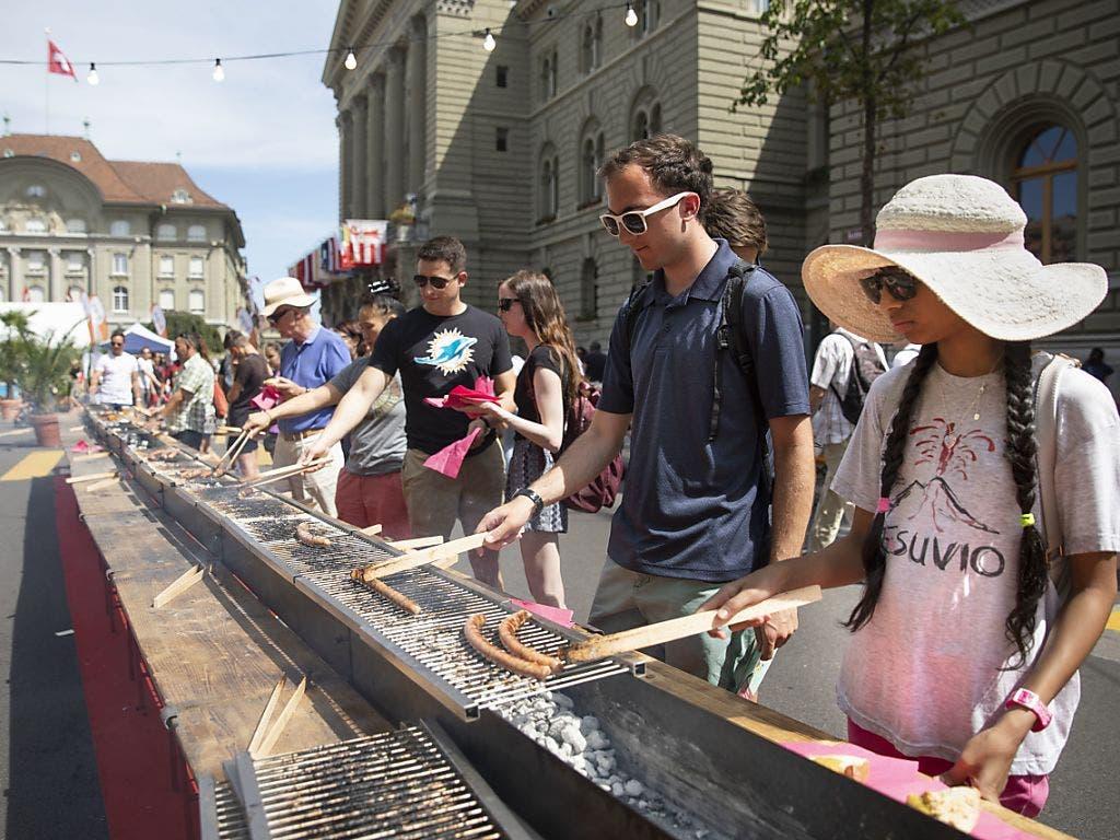 Vereinigtes Brutzeln: Besucher grillen Steaks und Würste vor dem Bundeshaus in Bern. (Bild: Keystone/PETER KLAUNZER)