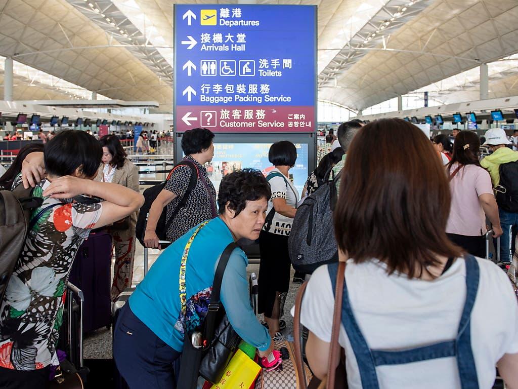 Anstehen am Check-In-Schalter: Am Hongkonger Flughafen wurde der Betrieb wieder aufgenommen. (Bild: KEYSTONE/EPA/MIGUEL CANDELA)