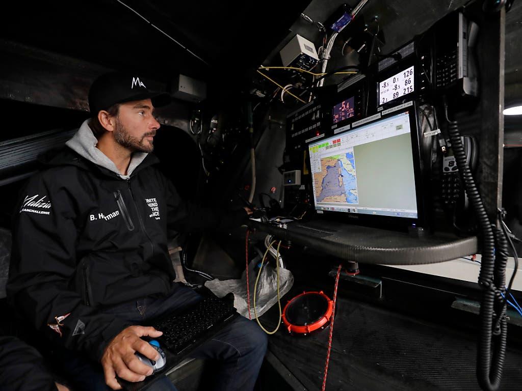 Kaum Platz unter Deck: Kapitän Boris Herrmann an den Navigationsinstrumenten im Rumpf der Renn-Jacht. (Bild: KEYSTONE/AP/KIRSTY WIGGLESWORTH)