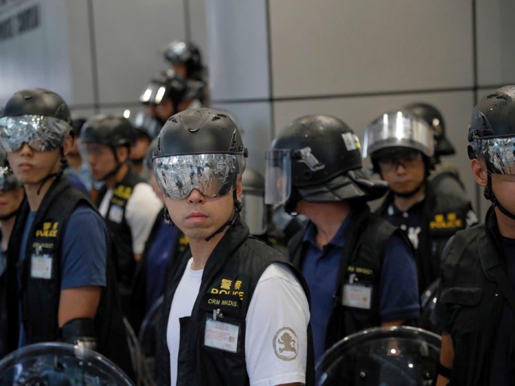 Polizisten schützen sich bei den Protesten in Hongkong mit Spezialbrillen gegen allfällige Laserattacken. (Bild: KEYSTONE/AP/KIN CHEUNG)