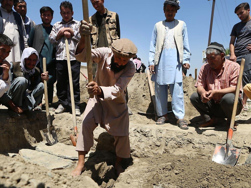 Ein Afghane hebt ein Grab für eine beim Anschlag getötete dreiköpfige Familie aus. (Bild: KEYSTONE/EPA/JAWAD JALALI)