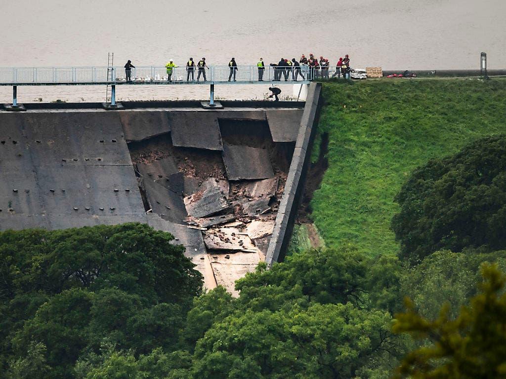 Mit Sandsäcken gegen die drohende Flut: Einsatzkräfte bei der Arbeit am bereits beschädigten Damm in Whaley Bridge, Grafschaft Cheshire. (Bild: KEYSTONE/AP PA/DANNY LAWSON)