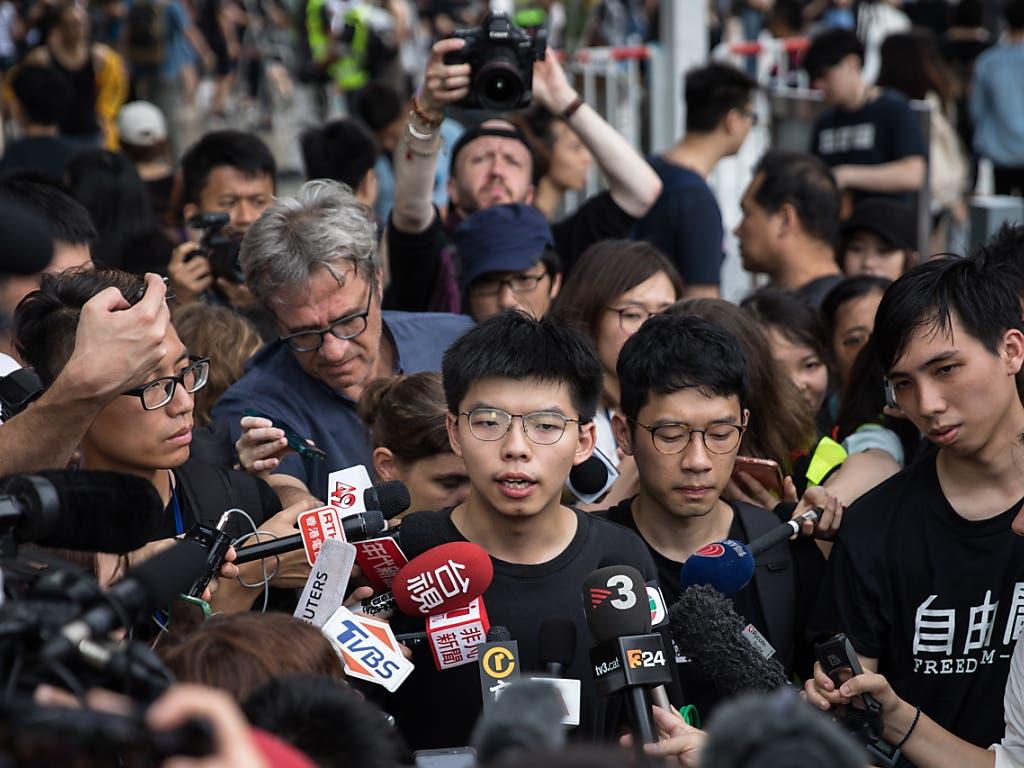 Der Hongkonger Aktivist Joshua Wong (Bildmitte) ist am Freitagmorgen in Polizeigewahrsam genommen worden. (Bild: KEYSTONE/EPA/JEROME FAVRE)
