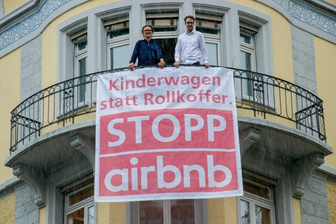 SP-Grossstadtrat Cyrill Studer Korevaar (links) und SP-Kantonsrat David Roth lassen von einer Airbnb-Wohnung an der Waldstätterstrasse ein Transparent hängen. (Bild: Beatrice Vogel, Luzern, 6. August 2019)