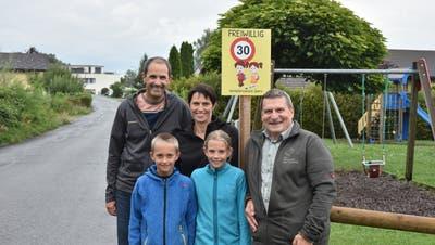 Melina und Dario hoffen zusammen mit ihren Eltern Patricia und Marco Vögel und Verkehrsvereins-Präsident Arnold Rossi (rechts), dass die Hinweistafeln «Freiwillig-Tempo 30» Autolenker zu rücksichtsvollem Verhalten auf der Wohnstrasse motivieren. (Bild: Thomas Schwizer)