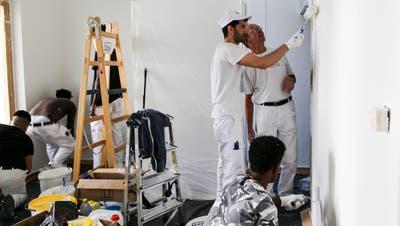 Malermeister Urs Giezendanner (hinten rechts) schaut bei der Arbeit seiner Schützlinge genau hin. (Bild: Ines Biedenkapp)