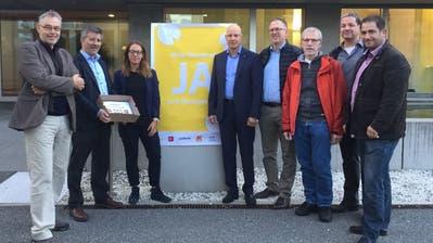 Die Übergabe der Unterschriften, das «Ja zum Einwohnerrat»-Plakat hängt auch schon (von links): Erwin Rast (SP), Sandor Horvath (GLP),Gemeindeschreiber-Substitutin Barbara Getzmann, Gemeindeschreiber Roland Baggenstos, Patrick Gunz (CVP), Peter Noser (Grüne), René Friedrich (FDP) und Stefan Bühler (SVP). (Bild: hor, Ebikon 27. September 2019)