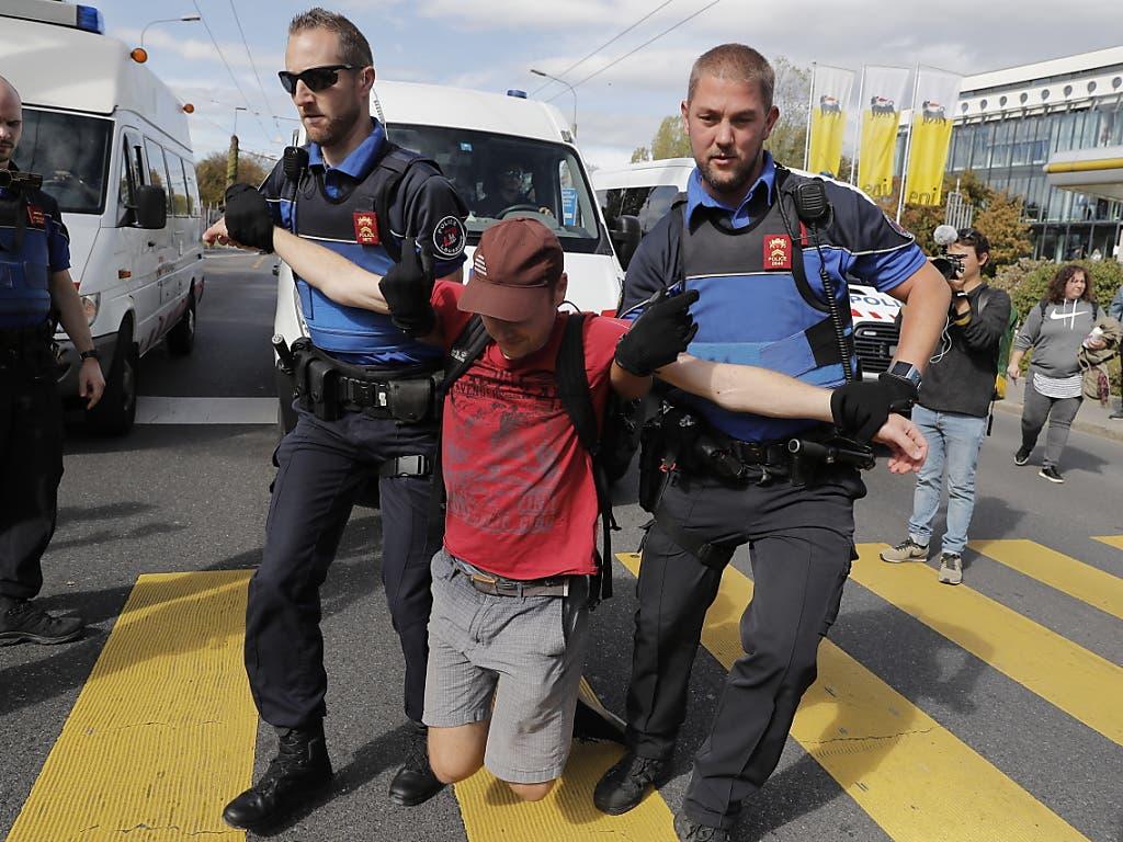 Ein Teilnehmer der Klimademonstration in Lausanne wird von der Polizei weggetragen. (Bild: KEYSTONE/EPA KEYSTONE/CYRIL ZINGARO)