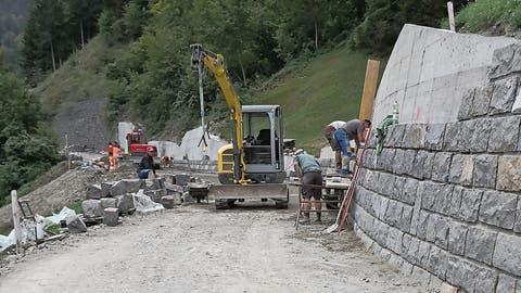 Equipen arbeiten an der Wiesenbergstrasse: Die erste Gruppe ist an der Natursteinverkleidung der Stützmauer und die zweite Gruppe erstellt die Planie für den folgenden Belagseinbau. (Bild: PD)