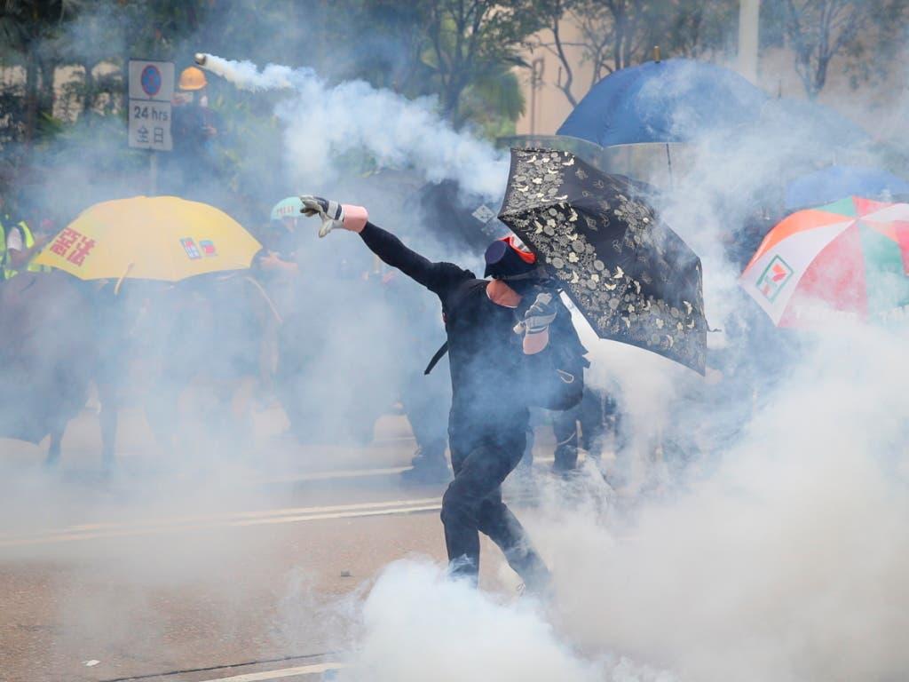 Protestierende Regierungsgegner in Hongkong werfen Tränengaspatronen zurück zu den Polizisten. (Bild: KEYSTONE/EPA/FAZRY ISMAIL)