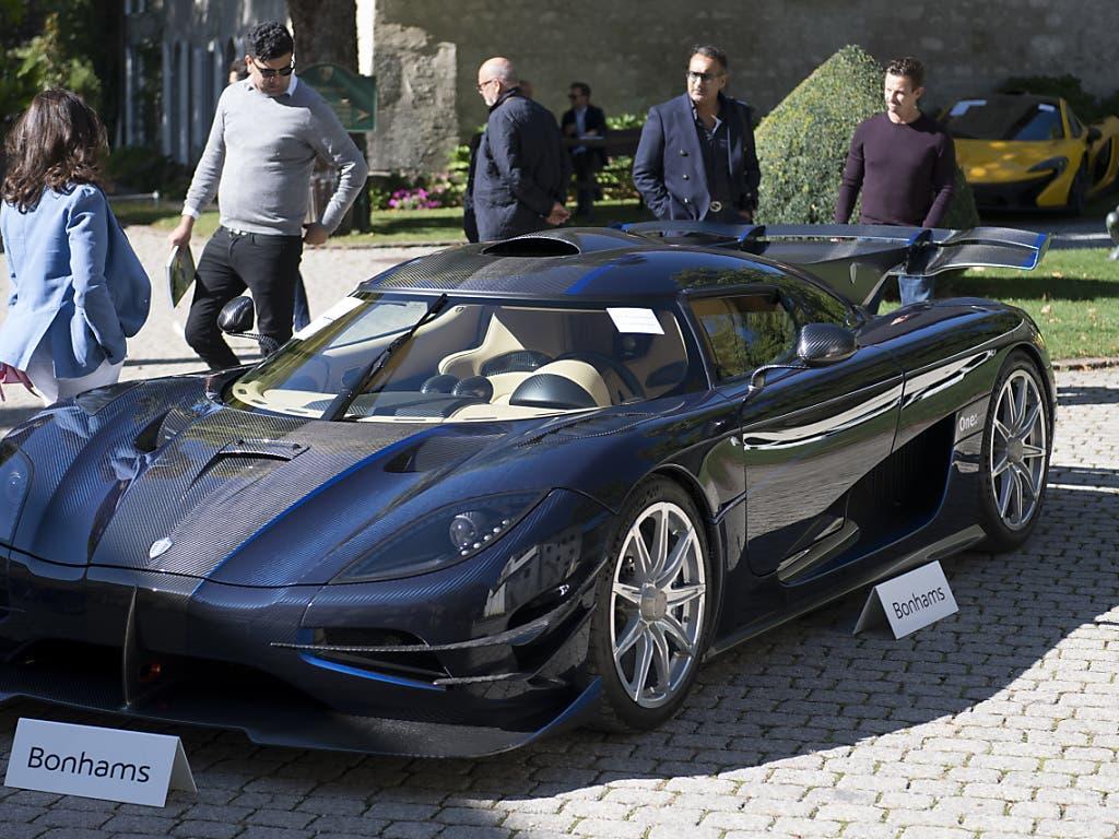 Interessenten begutachten einen Koenigsegg One, einer von 25 Luxuswagen des ältesten Sohnes des Präsidenten von Äquitorialguinea, der am Sonntag bei Genf versteigert wurde. (Bild: KEYSTONE/LAURENT GILLIERON)
