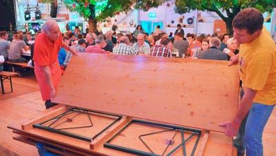 Roland Bartholdi und Heinz Brauchli räumen die Festbankgarnituren weg. Im Hintergrund essen die Gäste immer noch ihre Güggeli. (Bild: Mario Testa)