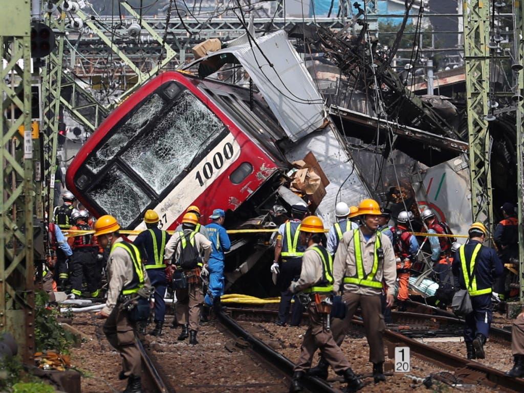Rettungsarbeiten nach der Kollision eines Zugs mit einem Lastwagen auf einem Bahnübergang in der Nähe von Tokio. (Bild: KEYSTONE/EPA JIJI PRESS)