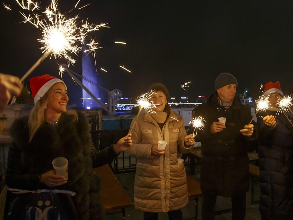 In Genf feierten Nachtschwärmer mit Wunderkerzen am See vor der bekannten Wasserfontäne «Jet d'Eau» den Jahreswechsel.