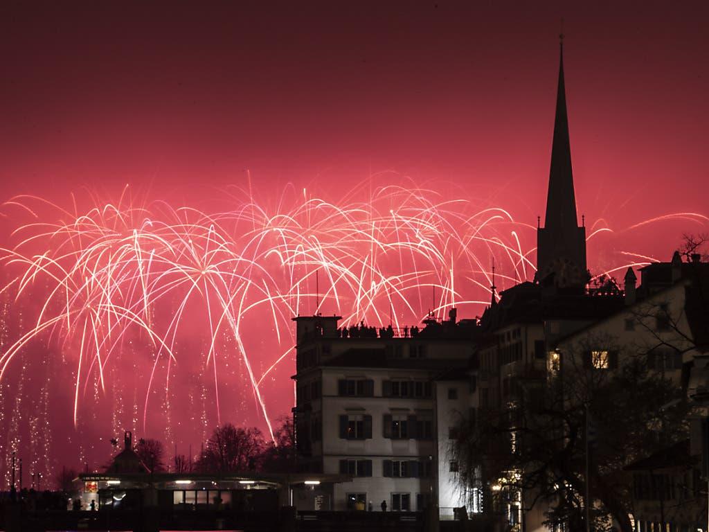 Das Neujahrs-Feuerwerk über dem Zürichsee erleuchtet den Nachthimmel über der Stadt rot.