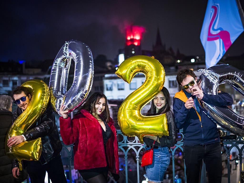 Menschen in Lausanne begrüssen das neue Jahr 2020. Im Hintergrund ist die Kathedrale rot beleuchtet.