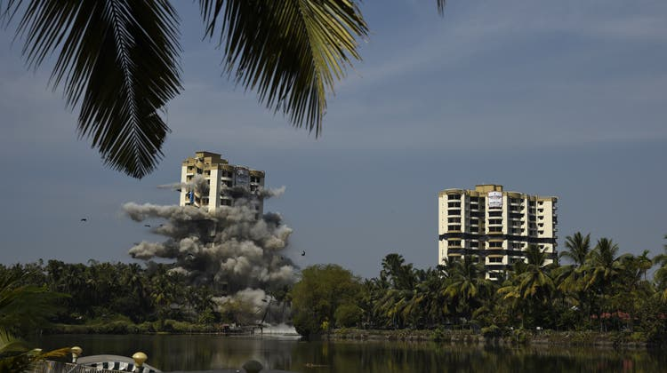 The first tower of water-front residential apartment Alpha Serene implodes moments before the second tower, on right, is blasted using controlled implosion in Kochi, India, Saturday, Jan. 11. 2020. Authorities in southern Kerala state on Saturday razed down two high-rise luxury apartments using controlled implosion in one of the largest demolition drives in India involving residential complexes for violating environmental norms. (AP Photo/R S Iyer) (R S Iyer, AP)