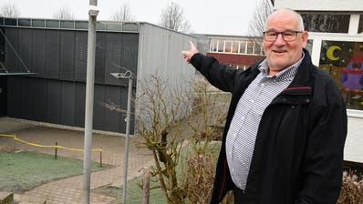 Schulpräsident PascalHollenstein zeigt auf das Gebäude, welches aufgestockt werden soll. ((Bild: Werner Lenzin))