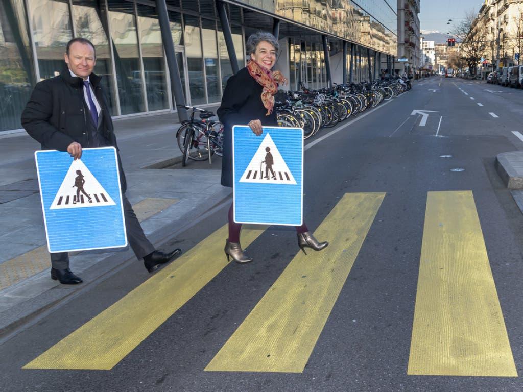 Der Genfer Staatsrat Serge Dal Busco (l.) und die Stadtpräsidentin Sandrine Salerno (r.) präsentieren auf einem Fussgängerstreifen die neuen Verkehrsschilder.