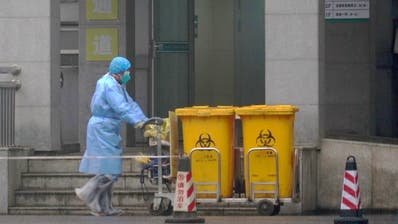 Staff move bio-waste containers past the entrance of the Wuhan Medical Treatment Center, where some infected with a new virus are being treated, in Wuhan, China, Wednesday, Jan. 22, 2020. The number of cases of a new coronavirus from Wuhan has risen over 400 in China Chinese health authorities said Wednesday. (AP Photo/Dake Kang) (Dake Kang / AP)