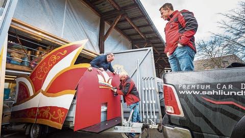 Erste Montage des neuen Narrenwagens namens «Mützli»: Martin «Kuri» Kuratli hält die Narrenkappe fest, damit sie Sepp Büttler anschrauben kann. Auf der Ladefläche der Zugmaschine steht Ivan Gubler und überwacht die Arbeiten. ((Bild: Andrea Stalder))