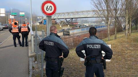 Polizisten sichern eine Autobahnüberführung in St.Gallen für die Durchfahrt des Konvois. (Bild: Urs Bucher)