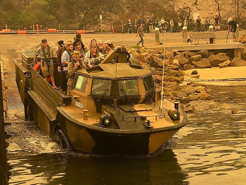 Menschen an der australischen Ostküste in der Kleinstadt Mallacoota werden mit Amphibienfahrzeugen des Militärs vor Buschfeuern in Sicherheit gebracht.