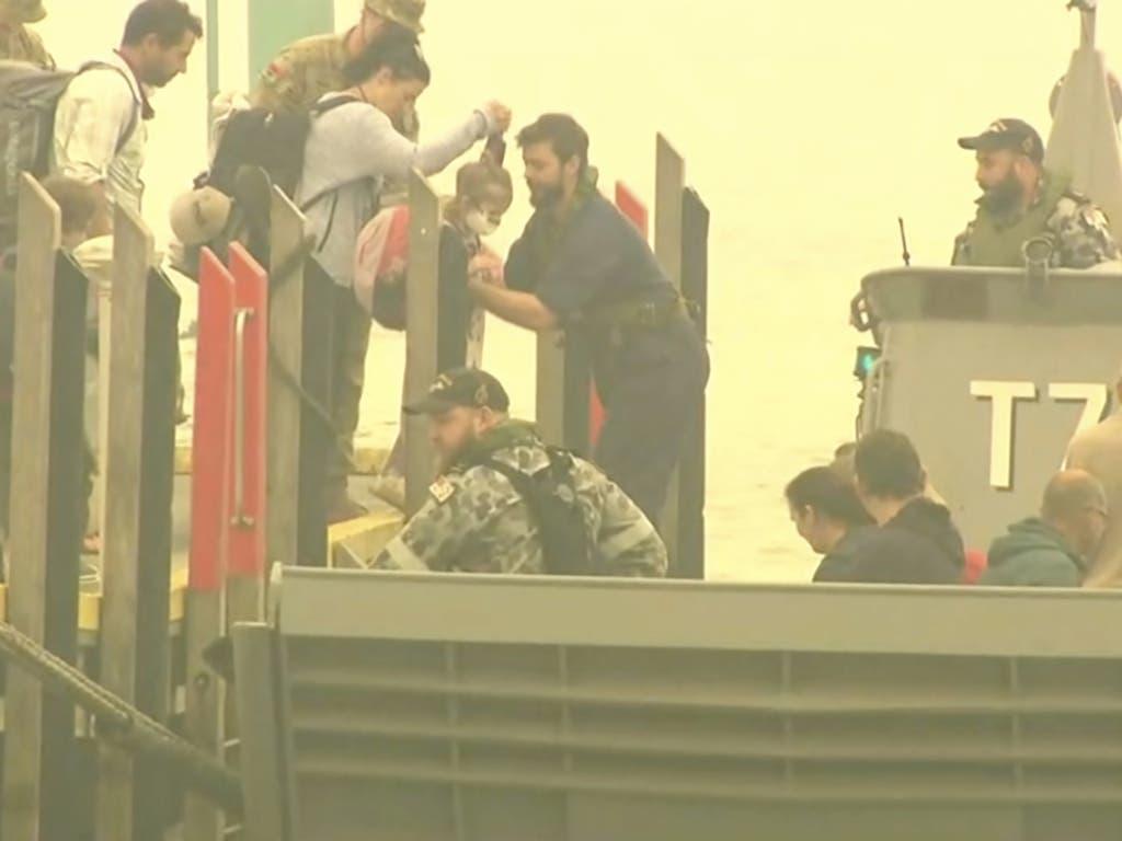 In der australischen Küstenstadt Mallacoota werden Menschen per Marineschiff vor Buschfeuern in Sicherheit gebracht.