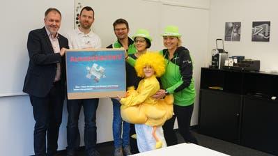Patrik Strässle von der Stadtkanzlei nimmt die Unterschriften von Simon Bürge, Markus Mauchle, Erika Miskos und Orkide Seven (von links, mit Maskottchen in Gelb) entgegen. (Johannes Wey)